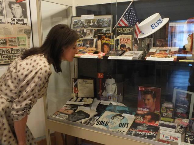 Ein Besucherin sieht siche eine Vitrine voller Elvis-Erinnerungsstücke im Volksmuseum in Burglengenfel an. Bild: Mark Iacampo